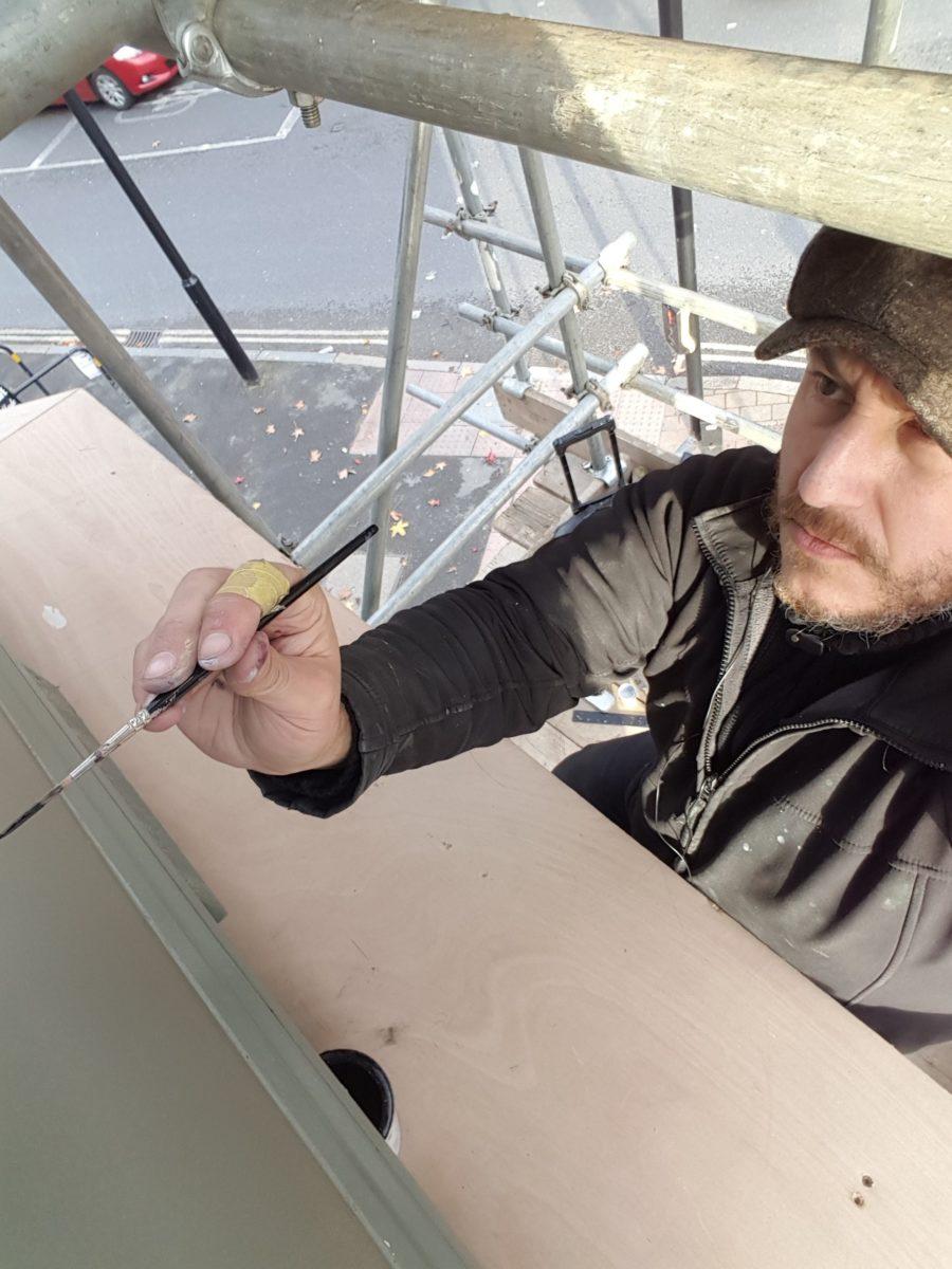 Signwriter London hard at work on scaffolding