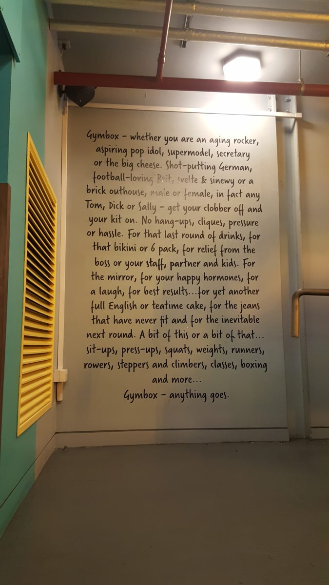 Sign writing quotes painted onto an internal wall at Gymbox by Traditional Signs of London